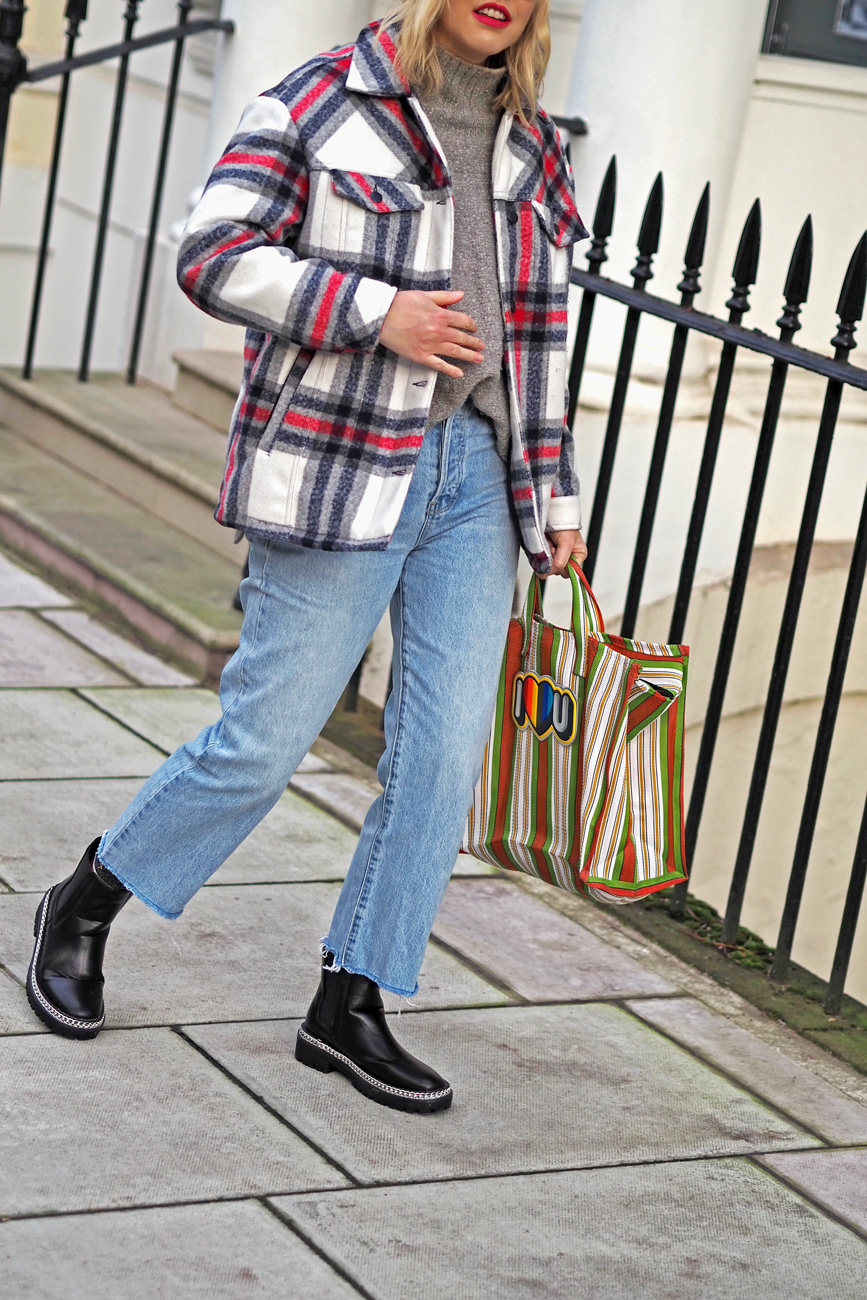 Alex Stedman of The Frugality wearing a red and white check over coat from Very along with a grey knitted roll-neck jumper from H&M, stone wash Gap jeans, Ace and Prince bag and black studded boots from Very.