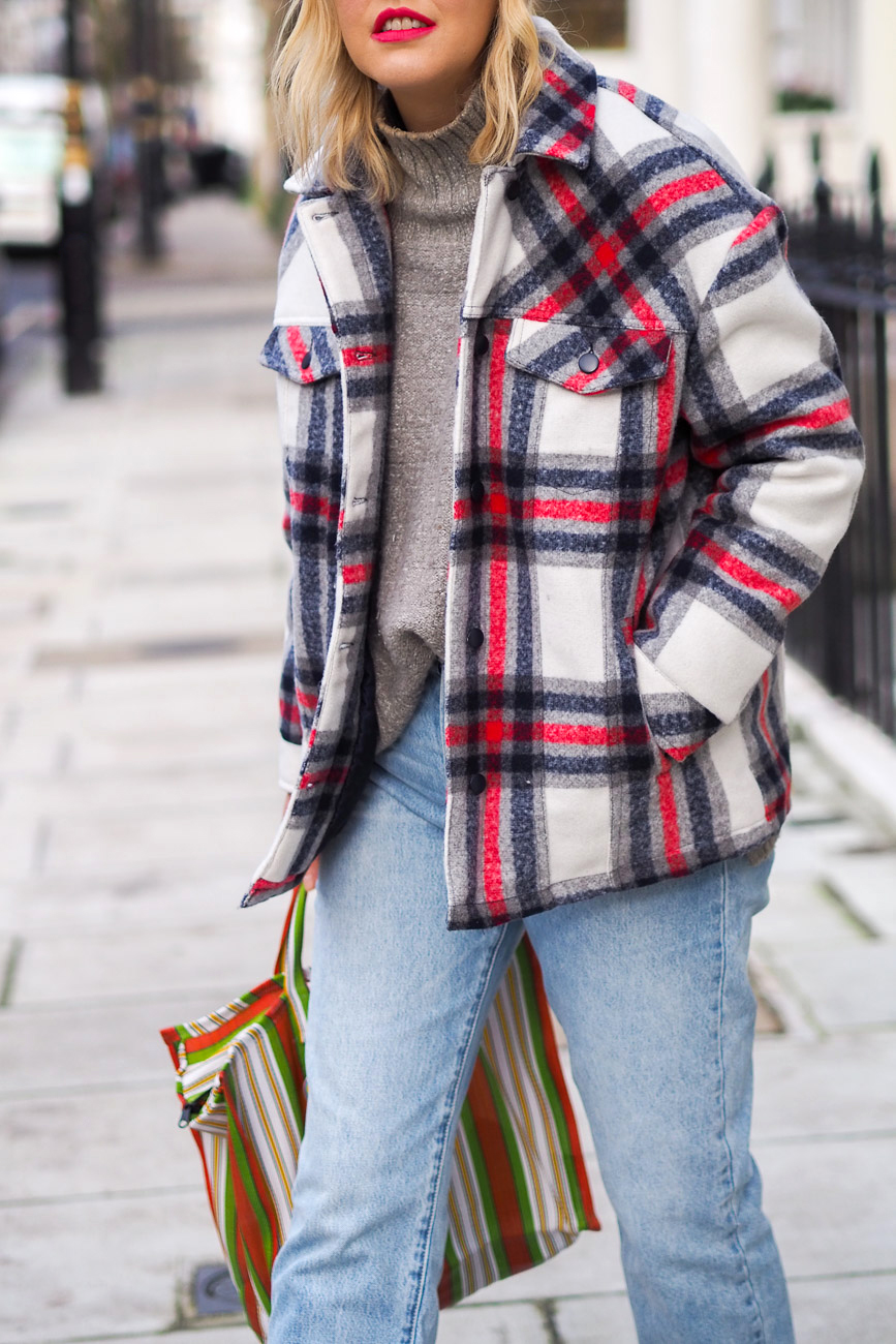 Alex Stedman of The Frugality wearing a red and white check over coat from Very along with a grey knitted roll-neck jumper from H&M, stone wash Gap jeans, Ace and Prince bag.