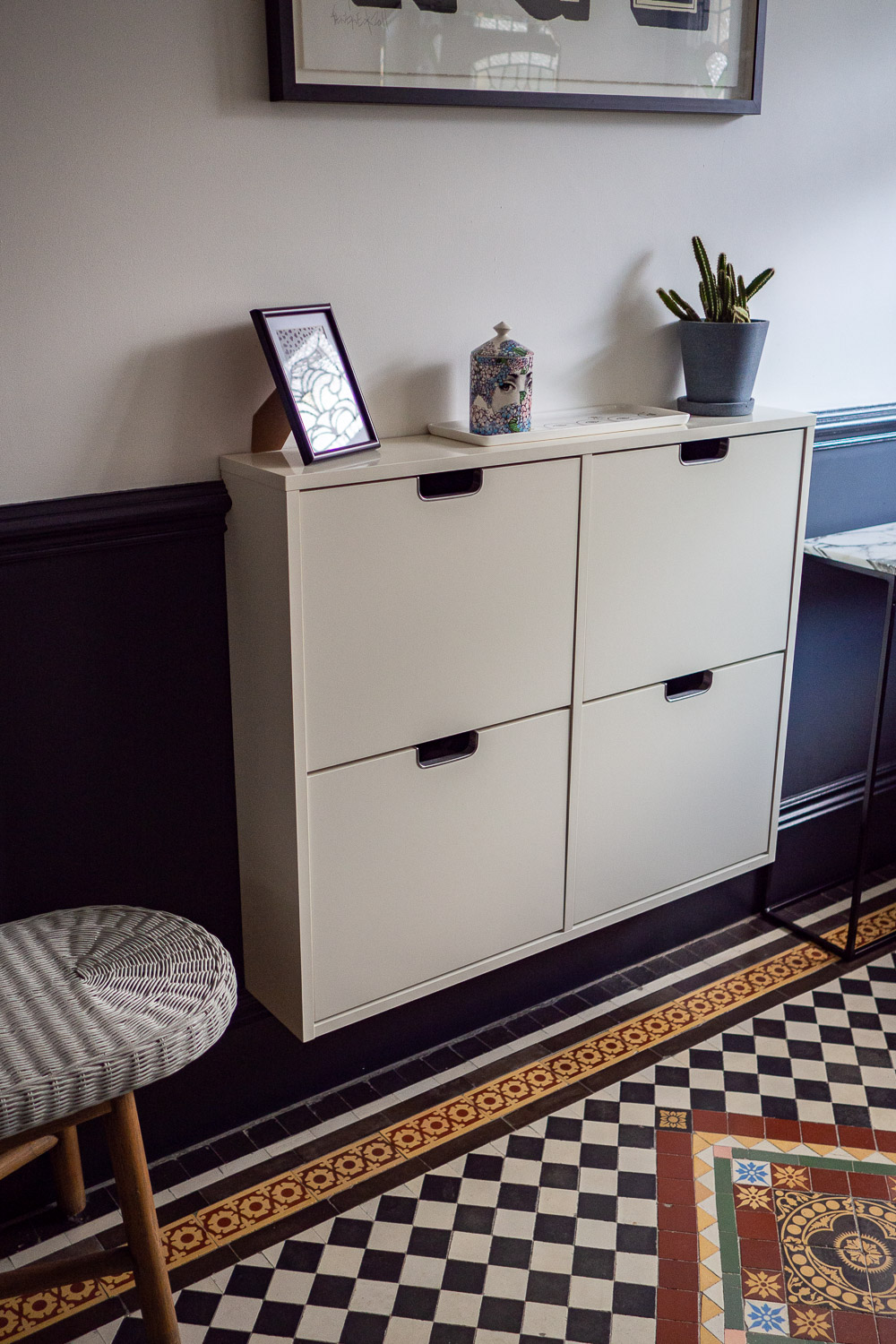 White Ikea STÄLL shoe storage cabinet. Fixed to the wall without its feet so that the skirting board isn't covered up.