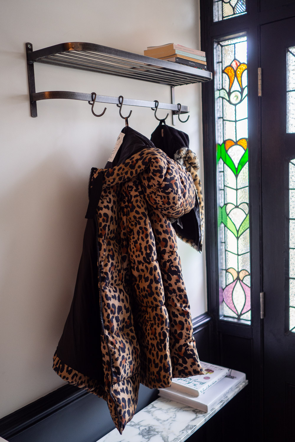 The Gap leopard puffer jacket and Gap baby leopard faux fur jacket hanging in the hallway.