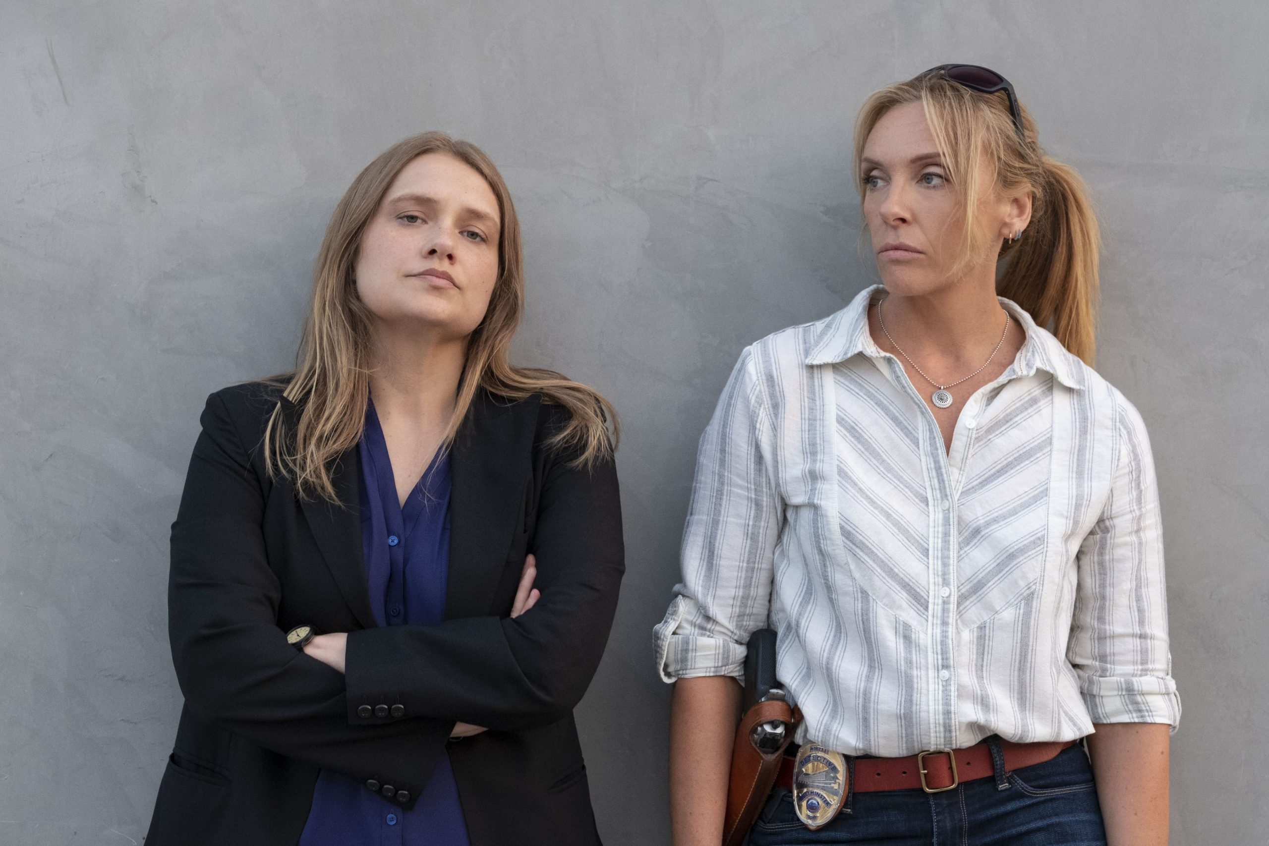 Merritt Wever and Toni Collette leaning against a wall as their characters Detective Karen Duvall and Detective Grace Rasmussen from the Netflix show 'Unbelievable'.