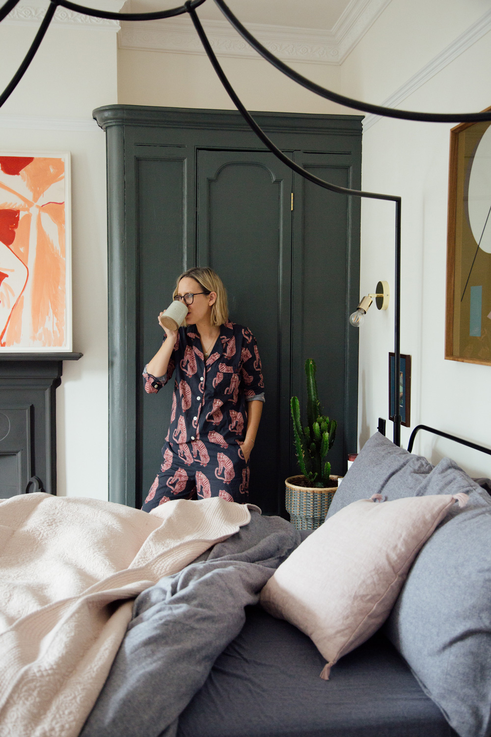 Alexandra Stedman wearing Desmond & Dempsey pyjamas in her bedroom whilst drinking a coffee.