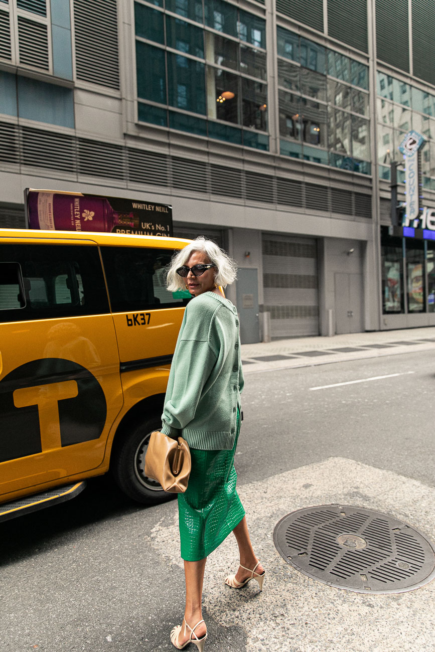 A New York fashion week guest wearing an oversized green cardigan styled with a green leather skirt.