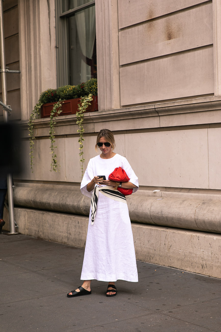 A New York fashion week guest wearing a simple full length white dress.