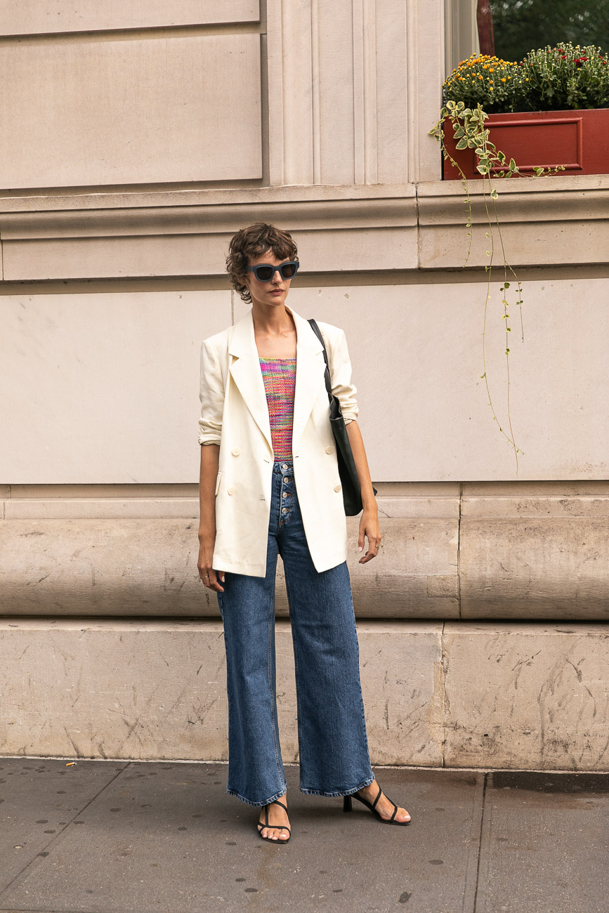 A Paris fashion week guest wearing an oversized white blazer, wide leg trousers and the barely there sandal.