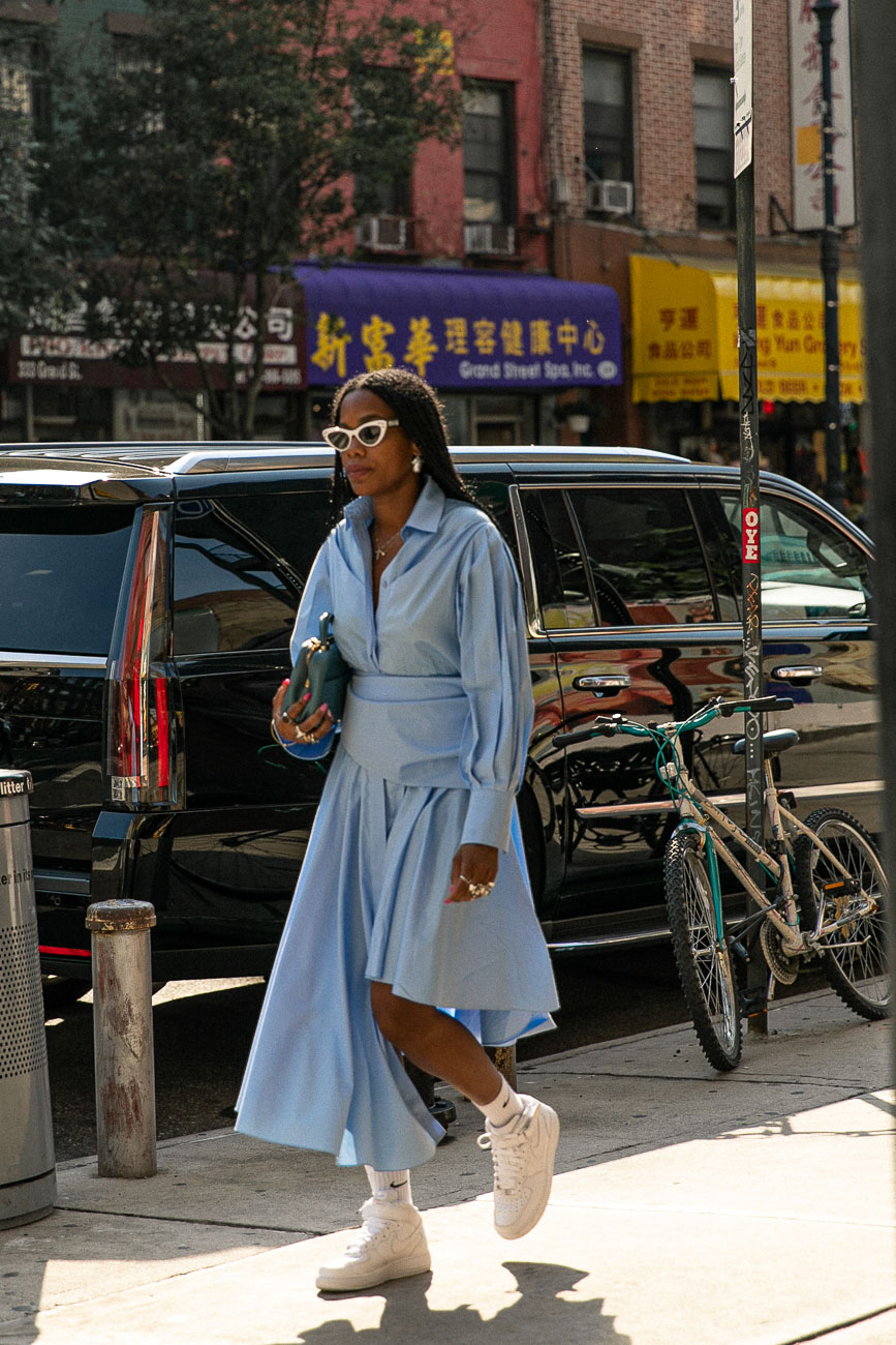 A New York fashion week guest wearing a full length light blue blouse dress with white nike high tops.