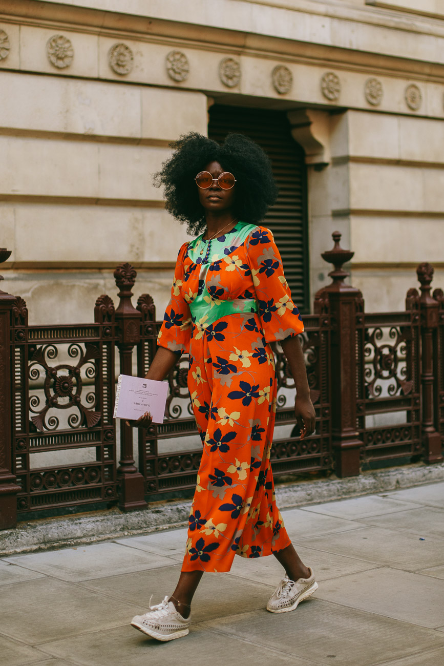 A London fashion week guest wearing a red floral print full length dress.