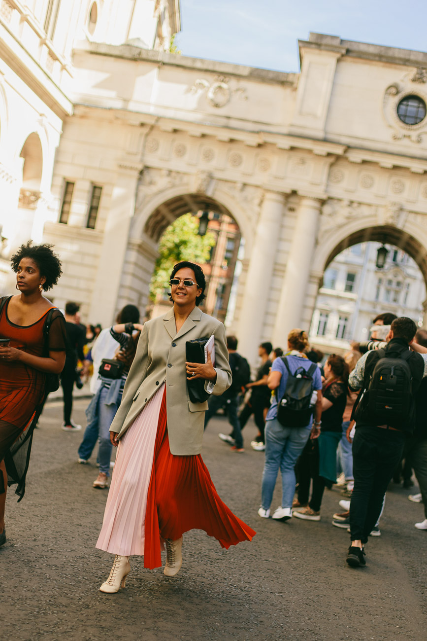 A London fashion week guest wearing a half pink, half red midi dress.