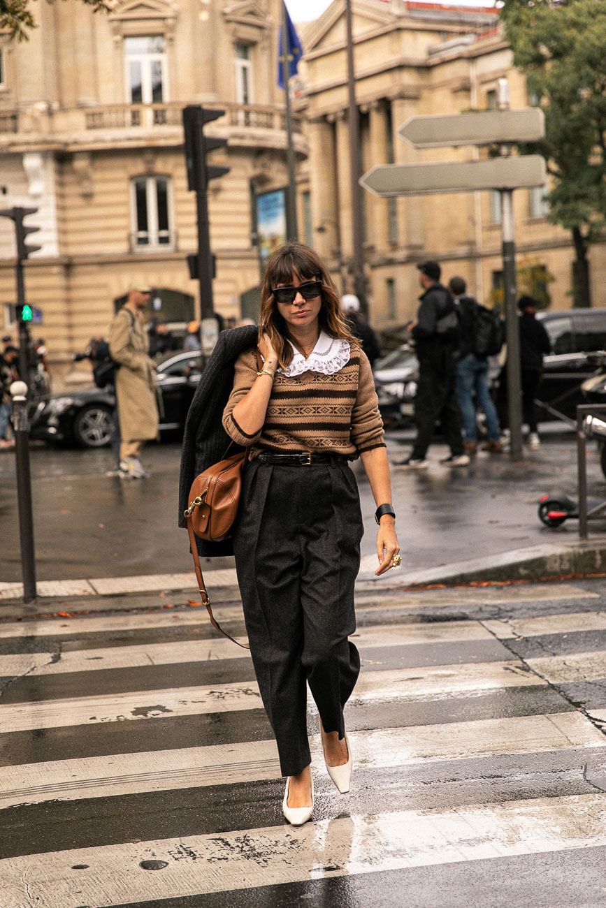 A Paris fashion week guest wearing high waisted dark grey flannel trousers with a brown knitted jumper tucked in.