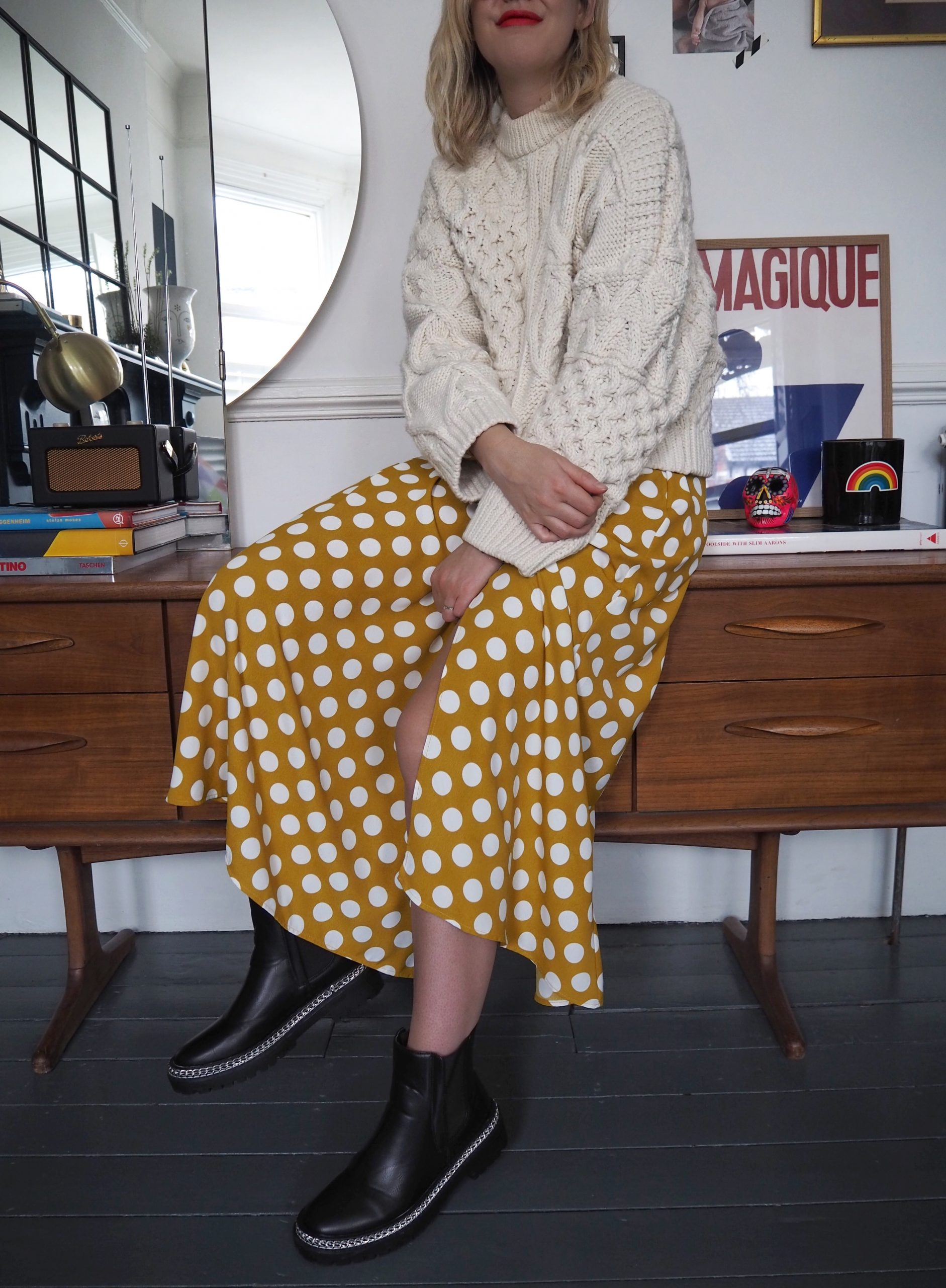 Alex Stedman of The Frugality wearing a yellow white polka dot Topshop dress. Styled with a white chunky knitwear jumper from H&M and black chunky studded boots from Very.