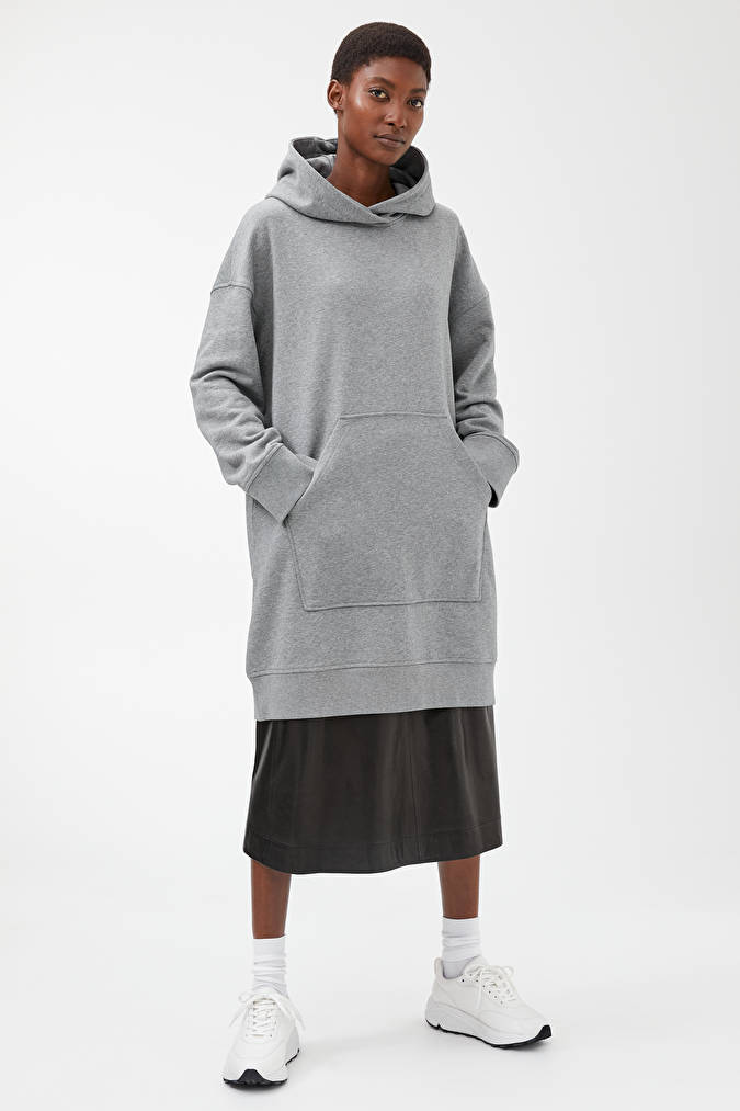 A model wearing a grey oversized hoodie from Arket.