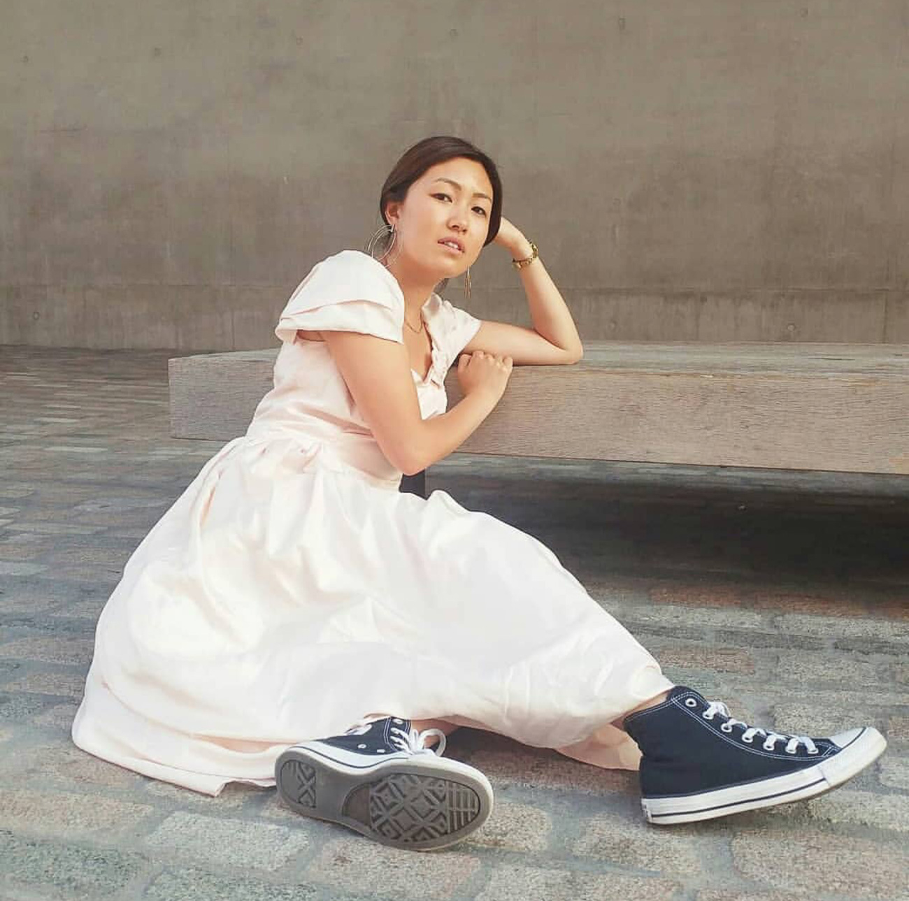 Queenie from Boutique by Shelter, Kings Cross, is wearing an unbranded vintage dress and her own Converse high-tops.