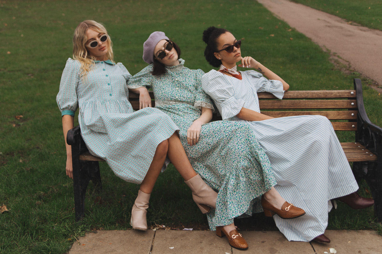 Three women sat on a park bench wearing long vintage dresses from the Another Matinee collection.